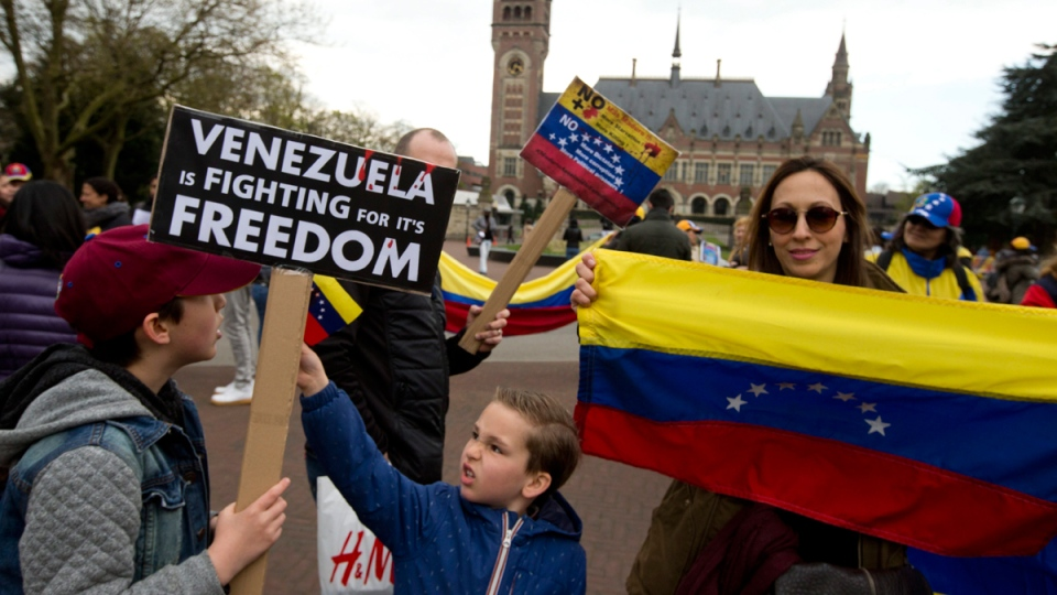 Human rights activists protest against the current situation in Venezuela outside the World Court, United Nations' highest judicial organ, rear, in The Hague, Netherlands, on April 19, 2017. (Peter Dejong / AP)