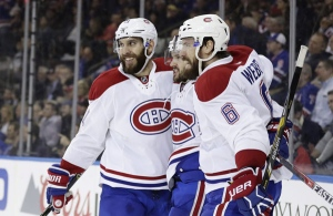 Montreal Canadiens' Dwight King, left, Shea Weber, right, and Torrey Mitchell celebrate a goal by Mitchell during the first period April 18, 2017, in New York. (AP Photo/Frank Franklin II)