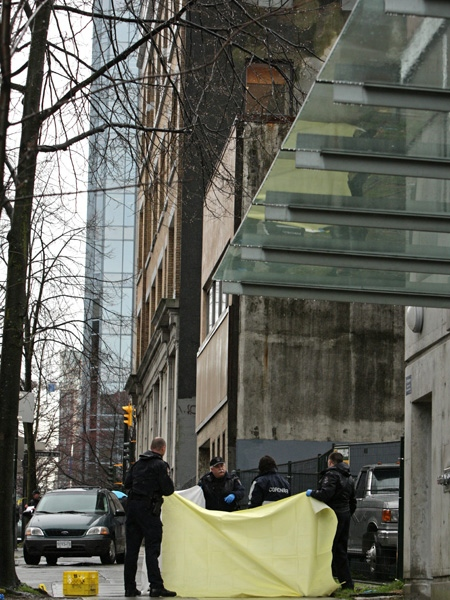 Police officers assist the coroner in removing a body after a man was shot and killed by police in Vancouver, B.C., on Friday, March 20, 2009. (CP/Darryl Dyck)