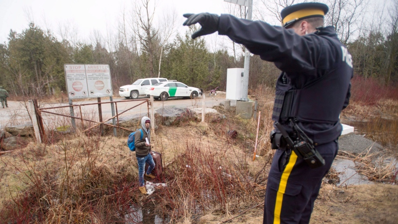 An RCMP officer warns a man to cross at the legal border crossing or he will be arrested at the border from New York into Canada on Wednesday, March 8, 2017 in Hemmingford, Quebec. THE CANADIAN PRESS/Ryan Remiorz