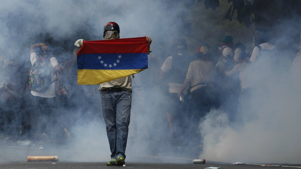 An anti-government protester holds a Venezuelan flag during clashes against security forces in Caracas, Venezuela on Wednesday, April 19, 2017. (AP / Ariana Cubillos)