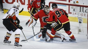 Anaheim Ducks' Nate Thompson, left, scores on Calgary Flames goalie Chad Johnson, centre, as Sam Bennett, right, looks on during first period NHL hockey round one playoff action in Calgary on Wednesday, April 19, 2017. (Jeff McIntosh / THE CANADIAN PRESS)