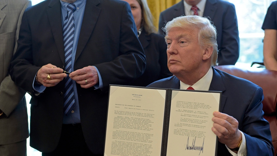 U.S. President Donald Trump show off the signed executive memorandum on investigation of steel imports, Thursday, April 20, 2017, in the Oval Office of the White House in Washington. (AP Photo/Susan Walsh)