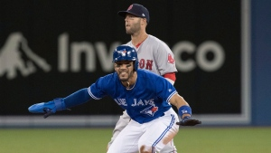 Toronto Blue Jays Devon Travis, front, slides in safe at second base as Boston Red Sox second baseman Dustin Pedroia looks on during the third inning of their MLB American League baseball game in Toronto on Thursday, April 20, 2017. (THE CANADIAN PRESS / Fred Thornhill)