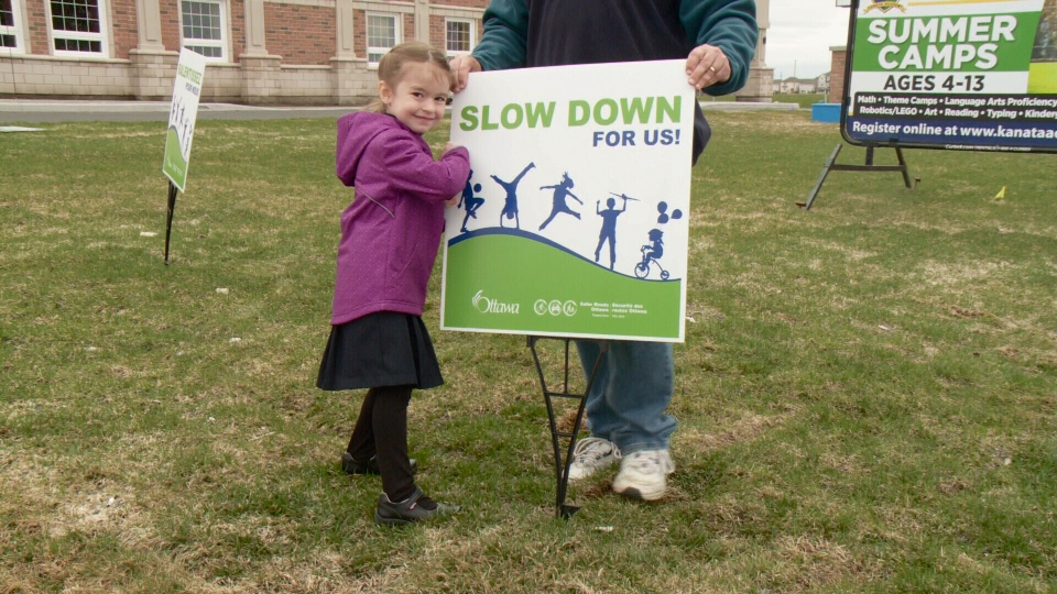 Kanata Academy student Julia Billie places a sign in the front lawn of her school encouraging drivers to slow down  on Thurs. April 20, 201