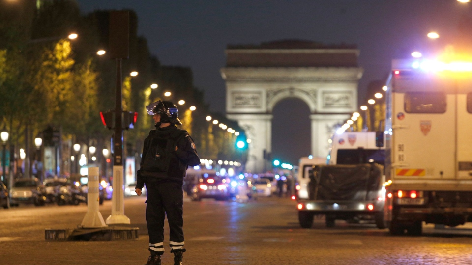 A police officer stands guard after a fatal shooting on the Champs Elysees in Paris, France, Thursday, April 20, 2017. French media are reporting that two police officers were shot Thursday on the famed shopping boulevard. Many police vehicles could be seen on the avenue that passes several of the city's most iconic landmarks. (AP Photo/Thibault Camus)