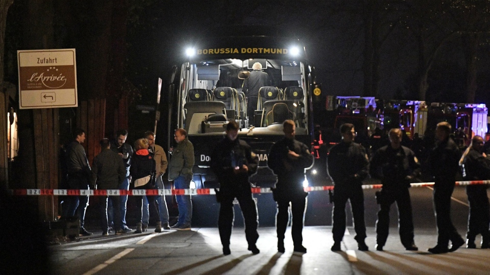 Police officers stand in front of Dortmund's damaged team bus after explosions which injured two people before the Champions League quarterfinal soccer match between Borussia Dortmund and AS Monaco in Dortmund, western Germany on April 11, 2017. (AP / Martin Meissner)