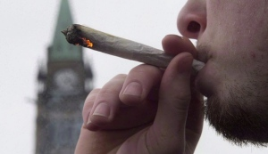 A man lights a marijuana joint as he participates in the 4/20 protest on Parliament Hill in Ottawa, April 20, 2015. Finance Minister Bill Morneau says the Liberal government has not decided how to tax marijuana, but is instead focused on making sure it stays out of the hands of children and criminals.(THE CANADIAN PRESS/Adrian Wyld)