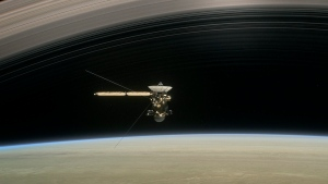 "This image made available by NASA in April 2017 shows a still from the short film ""Cassini's Grand Finale,"" with the spacecraft diving between Saturn and the planet's innermost ring. (NASA/JPL-Caltech via AP)"