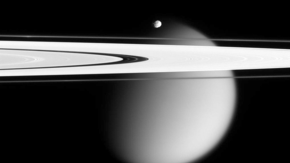 This image made by the Cassini spacecraft and provided by NASA on March 12, 2006, shows two of Saturn's moons, the small Epimetheus and smog-enshrouded Titan, with Saturn's A and F rings stretching across the frame. (AP Photo/NASA)