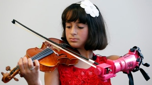 Ten-year-old Isabella Nicola Cabrera plays her violin with her new prosthetic at the engineering department of George Mason University in Fairfax, Va., Thursday, April 20, 2017.(AP Photo/Steve Helber)