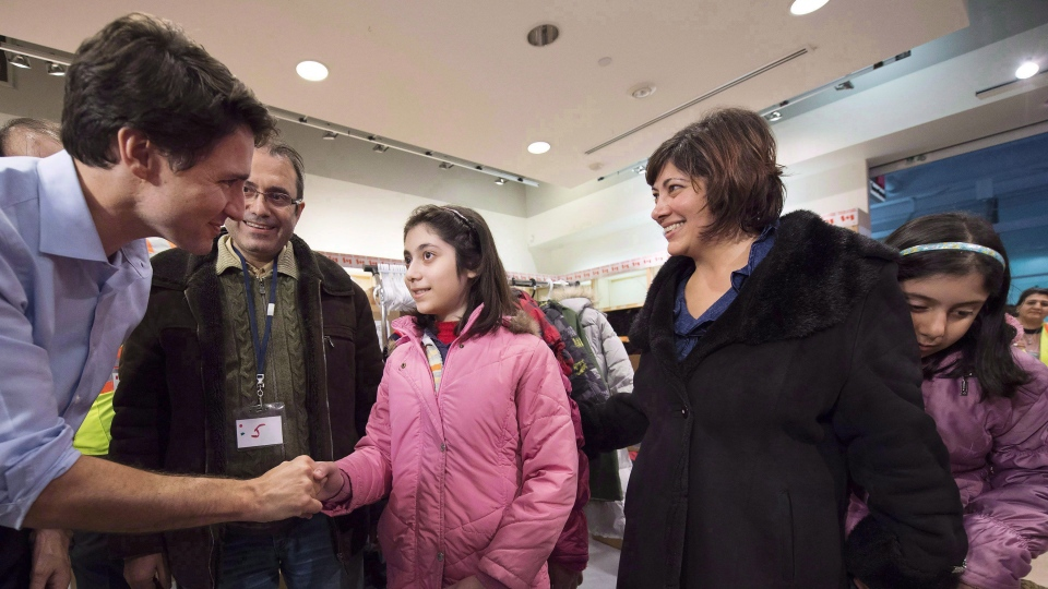 Prime Minister Justin Trudeau greets newly-arrived Syrian refugees Lucie Garabedian, her father Vanig Garabedian, mother Anjilik Jaghlassian and sister Anna-Maria Garabedian, right, at Toronto Pearson International airport on Dec. 11, 2015. (Nathan Denette / THE CANADIAN PRESS)