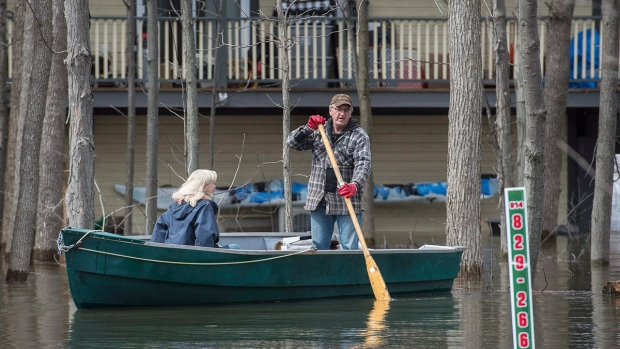 A man and woman use a boat to move along a street in the town of Rigaud, Que., west of Montreal, Thursday, April 20, 2017, following flooding in the area. (THE CANADIAN PRESS/Graham Hughes)