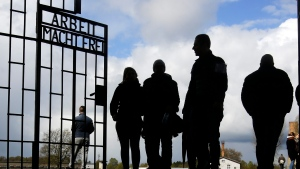 People enter the Sachsenhausen Nazi death camp through the gate with the inscription 'Arbeit macht frei' (work sets you free) for commemorations of the 72nd anniversary of the liberation of the camp in Oranienburg, about 35 kilometres north of Berlin Sunday, April 23, 2017. (AP / Markus Schreiber)