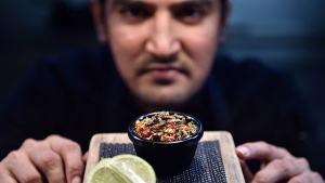 Sous-chef Nowshad Alam Rasel displaying a signature cricket dish at a restaurant in Sydney. (Saeed Khan / AFP)