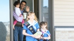 Girl Guides Kiera Kucherhan (right) and Sienna Kucherhan (centre) are selling cookies in Kanata, Ont. to send to Canadian troops deployed overseas. (CTV Ottawa)