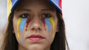 A woman with her face painted in the colours of Venezuela's national flag attends a silent protest in homage to the at least 20 people killed in unrest generated after the nation's Supreme Court stripped congress of its last powers, a decision it later reversed, as she marches to the Venezuelan Episcopal Conference in Caracas, Venezuela on Saturday, April 22, 2017. (AP / Ariana Cubillos)