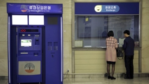 A man and woman stand at a counter next to a Ryugyong Commercial Bank automated teller machine at the Sunan International Airport in Pyongyang, North Korea on April 11, 2017. (AP / Wong Maye-E)