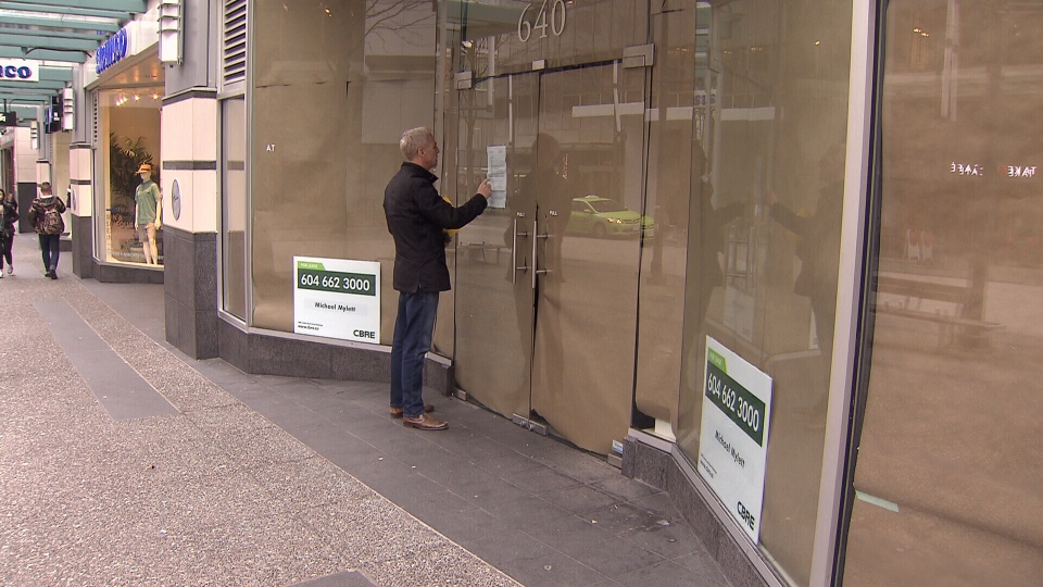 Ross McLaughlin reads a sign on the closed doors of what was formerly an Ella Shoes store. (CTV)
