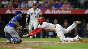 Los Angeles Angels' Cameron Maybin, right, scores on fielder's choice hit by David Hernandez as Toronto Blue Jays catcher Russell Martin makes a late tag during the fifth inning of a baseball game, Monday, April 24, 2017, in Anaheim, Calif. (AP / Mark J. Terrill)
