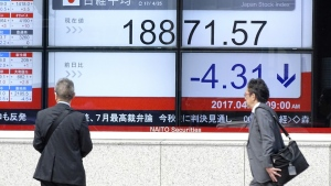 Men look at an electronic stock board showing Japan's Nikkei 225 index at a securities firm in Tokyo, Tuesday, April 25, 2017. (AP / Eugene Hoshiko)