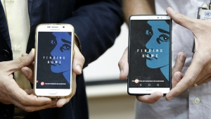 "Representative of the United Nations High Commissioner for Refugees (UNHCR) Malaysia Richard Towle, left, and Executive Creative Director of GREY Malaysia, Graham Drew, right, shows the application ""Finding Home"" on their phones during a launch at the UNHCR headquarters in Kuala Lumpur, Malaysia, Tuesday, April 25, 2017. (AP / Daniel Chan)"
