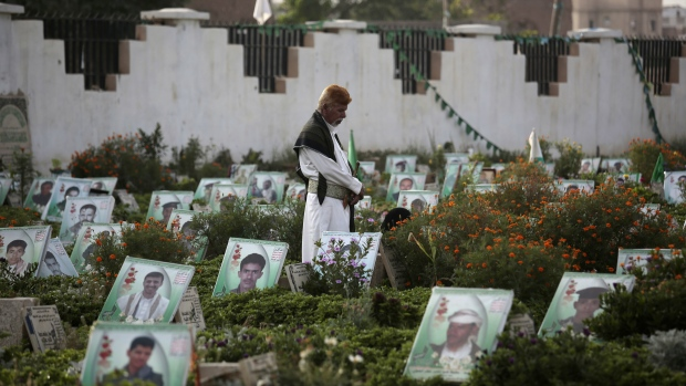 In this Sept. 12, 2016 file photo, a Yemeni man offers prayers at the portrait adorned grave of his relative who was killed in the ongoing conflict in Yemen, in Sanaa, Yemen. (AP / Hani Mohammed, File)