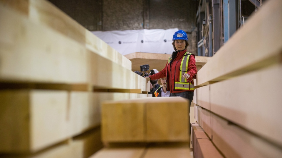 B.C. Liberal Leader Christy Clark stands on pieces of wood during a campaign stop at StructureCraft Builders in Delta, B.C., on Monday April 24, 2017. THE CANADIAN PRESS/Darryl Dyck
