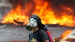 An anti-government protester stands in front of burning barricade on a highway in Caracas, Venezuela, Monday, April 24, 2017. (AP / Ariana Cubillos)