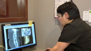 Dr. Shannon Davis reviews x-rays in her Calgary office