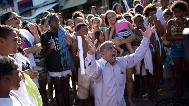 A resident shouts for peace during a protest against police and gang conflicts that leave residents in the crossfire at the Complexo de Alemao slum in Rio de Janeiro, Brazil, Tuesday, April 25, 2017. Residents are protesting after a youth died in a shootout early Tuesday. (AP Photo / Silvia Izquierdo)