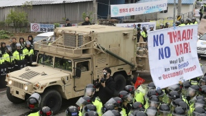 U.S. military vehicle moves past banners opposing a plan to deploy an advanced U.S. missile defence system called Terminal High-Altitude Area Defense, or THAAD, as South Korean police officers stand guard in Seongju, South Korea on Wednesday, April 26, 2017. (Kim Jun-hum / Yonhap)
