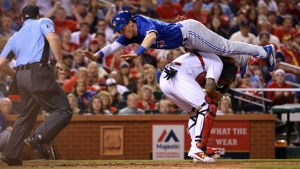 Toronto Blue Jays' Chris Coghlan scores, leaping over St. Louis Cardinals catcher Yadier Molina during the seventh inning of a baseball game Tuesday, April 25, 2017, in St. Louis. (Christian Gooden/St. Louis Post-Dispatch via AP)