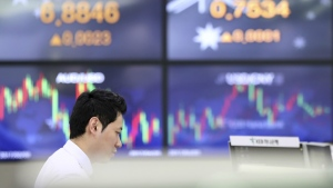 A currency trader watches monitors near screens showing the foreign exchange rates at the foreign exchange dealing room in Seoul, South Korea, Wednesday, April 26, 2017. (AP / Lee Jin-man)