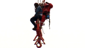Rescue crews reach the woman stranded on the crane in downtown Toronto, Wednesday, April 26, 2017.