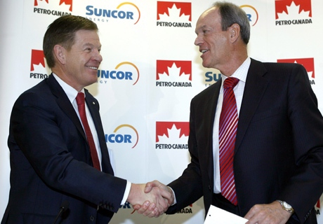 Rick George, left, Suncor president and CEO, and Ron Brenneman, Petro-Canada president and CEO, shake hands after a press conference announcing the merger of the two companies in Calgary on Monday March 23, 2009. (Larry MacDougal / THE CANADIAN PRESS)