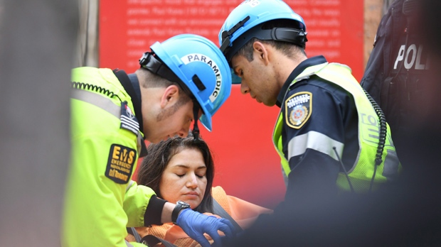 A woman is placed on a stretcher after being rescued from a downtown Toronto crane early Wednesday, April 26, 2017. Some streets in the downtown core were closed as dozens of construction workers and commuters gazed skyward to watch police and firefighters try to rescue a woman who got stuck atop a tall construction crane during the night. THE CANADIAN PRESS/Frank Gunn