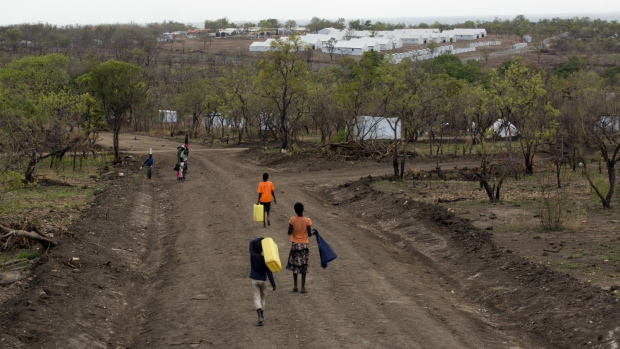 South Sudanese children carry water jugs down a road in the new Imvepi refugee settlement in northern Uganda on Thursday, April 6, 2017. (AP / Jerome Delay)