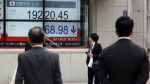 A man looks at an electronic stock board showing Japan's Nikkei 225 index at a securities firm in Tokyo on Thursday, April 27, 2017. (AP / Eugene Hoshiko)