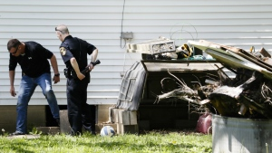 Police search a home where they say a man with mental health problems kidnapped a neighbour and kept her trapped in a small grave-like pit in his backyard shed in Blanchester, Ohio on Wednesday, April 26, 2017. (AP / John Minchillo)