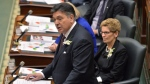 Ontario Finance Minister Charles Sousa, left, delivers the Ontario 2016 budget next to Premier Kathleen Wynne, right, at Queen's Park in Toronto on Thursday, Feb. 25, 2016. Ontario's Liberal government will release its first balanced budget in a decade on Thursday, with a host of new spending measures focused on pocketbook issues that it hopes will resonate with voters heading into an election year. (Nathan Denette / THE CANADIAN PRESS)
