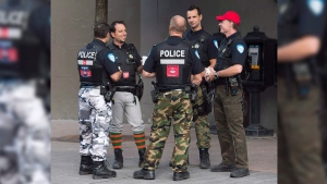 Montreal Police officers are shown on a street in Montreal on Aug. 7, 2014. (Graham Hughes / THE CANADIAN PRESS)