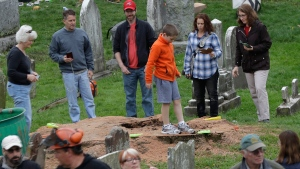 People stand on the stump where a 600-year-old oak tree once stood in Bernards, N.J., on April 26, 2017. (Julio Cortez / AP)