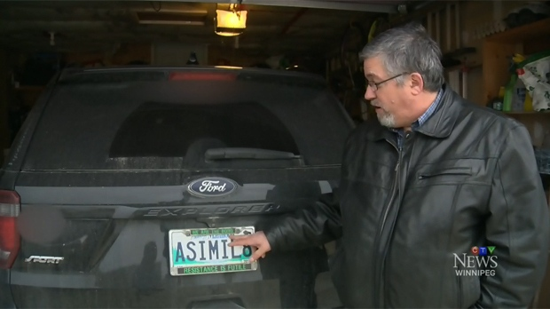 Nick Troller stands beside his licence plate in Winnipeg, Man.
