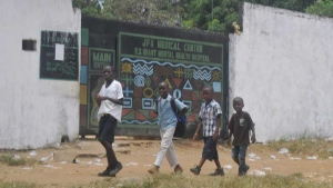 In this photo taken Friday, March. 31, 2017, children walk past JFK Medical centre in Monrovia, Liberia. (AP Photo/ Abbas Dulleh)