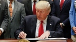 U.S. President Donald Trump signs an Executive Order in the Roosevelt Room of the White House in Washington, on April 28, 2017. (Pablo Martinez Monsivais / AP)