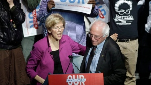 Sens. Elizabeth Warren left, and Bernie Sanders, right, greet one another during a rally, in Boston, on Friday, March 31, 2017. (AP Photo/Steven Senne)