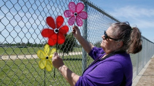 Donna Farrell places plastic flowers to remember Fusako Petrus on a fence surrounding the track of Highlands High School, Friday, April 28, 2017, in Sacramento, Calif. Petrus, 86, was sexually assaulted and beaten to death during a morning walk around the track with a friend, Wednesday. (AP Photo / Rich Pedroncelli)