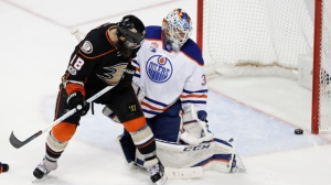 Edmonton Oilers goalie Cam Talbot, right, and Anaheim Ducks right wing Patrick Eaves watch as a shot bounces off the goal post during the third period in Game 2 of a second-round NHL hockey Stanley Cup playoff series in Anaheim, Calif., Friday, April 28, 2017. (AP Photo/Chris Carlson)