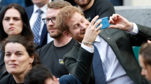 Prince Harry, right, uses a smartphone to take a photograph as he sits with competitors from the 2014 and 2016 Invictus Games in the crowd watching the annual Army Navy armed forces rugby match at Twickenham, west London, on Saturday, April 29, 2017. (Adrian Dennis/ Pool via AP)
